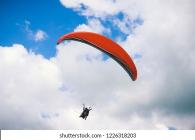 Paraglider flying in cloudy sky