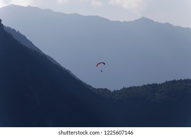 Paraglider flying in the early morning mists in amongst the mountains above Lake Annecy France