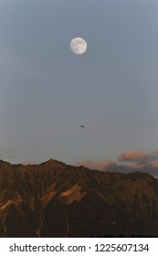 Paraglider flying in the evening light amongst the mountains with the moon in the sky Annecy France