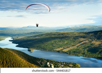 Paraglider flying high in the sky over a lake, forest and a mountain landscape. Sweden.
