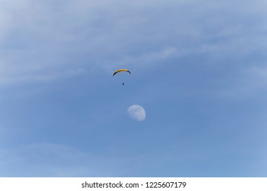 Paraglider flying just above the moon in the sky above Lake Annecy  France