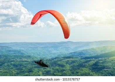 Paraglider flying on the beautiful sunny sky over the green mountains in Croatia. Buzet, Raspadalica, May 2017.