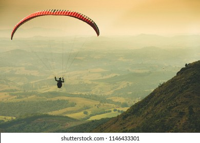 Paraglider flying on the beautiful sunny sky over the green mountains in Poços de Caldas, Minas Gerais, Brazil, June 2018