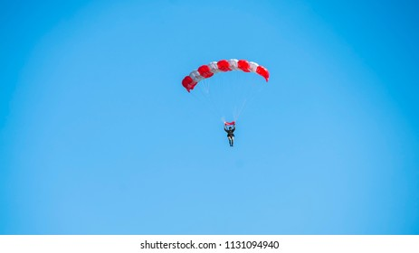 Paraglider flying on red-colored parachute in blue clear sky at a bright sunny summer day. Active lifestyle, extreme hobbies