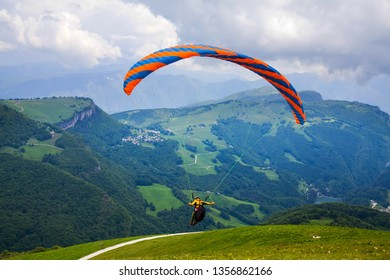 Paraglider flying over the breathtaking scenery italian alps.