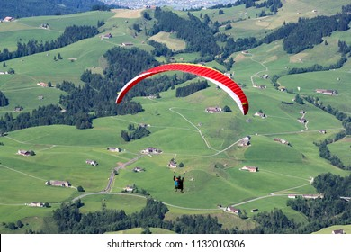 Paraglider flying over the field in teh Alps mountain area