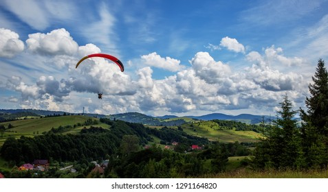 Paraglider flying over mountains during summer day