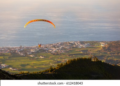 a paraglider flying over Ribeira Grande Azores at sunset