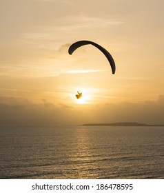 A paraglider flying over the sea at sunset.