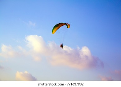 Paraglider flying over sea.Paraglider flies colorful paraglider in the blue sky.