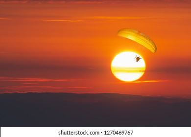 Paraglider flying with paramotor on dramatic sunset sky with big sun in orange . Concept for adventure extreme ultra light aviation copy space.