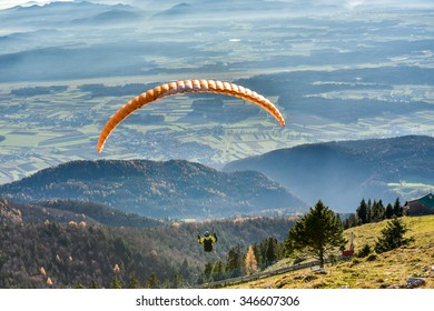 Paraglider is flying in the valley. Paragliding from the mountain with perfect view