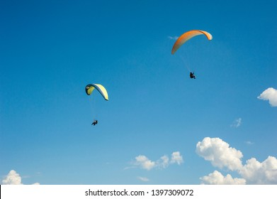 Paraglider flying wing in a blue sky. Two paragliders are flying in the blue sky against the background of clouds. Paragliding among the clouds on a sunny day.
