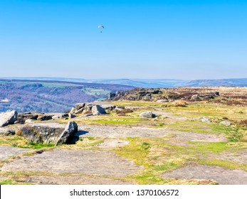 Paraglider flys over Curbar Edge, in the Derbyshire Peak District, on a haxy spring day.