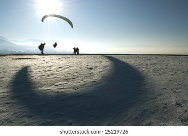 Para-glider gliding between the sun and a moon shaped shadow.