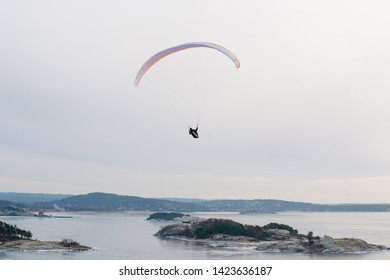Paraglider gliding over an ice cold fjord.