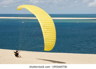 Parapente gonflant un parapente voilier sur le sable de la dune de Pyla avec une vue magnifique sur le bassin d'Arcachon dans l'océan Atlantique, département de la Gironde, France