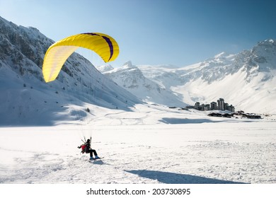 Paraglider landing on skis in Tignes, a ski resort in the french Alps