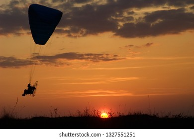 Paraglider lands on sunset. Paramotor silhouette flying at sunset