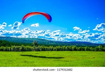 Paraglider on summer green mountain valley landscape. Summer green mountain valley paragliding. Paraglider in sky. Sky paraglider