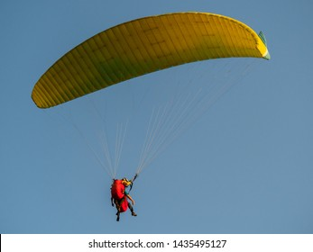 Paraglider with passanger flying in the blue sky.