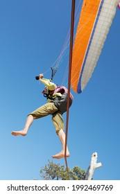 Pilote de parapente vu de dessous faisant des acrobaties sur une corde à la dune de Pyla en France