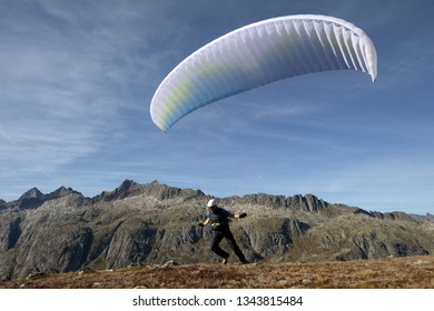 Paraglider Pilot takes off with his paraglider to take off and fly into the valley in the Swiss Alps