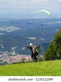 Paraglider running to take off from a mountain near Freiburg