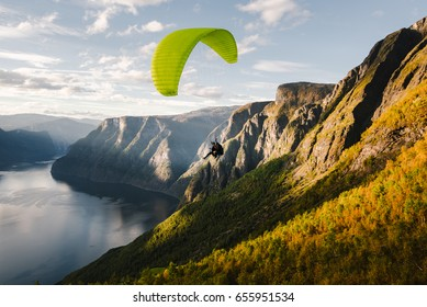 Paraglider silhouette flying over Aurlandfjord, Norway.