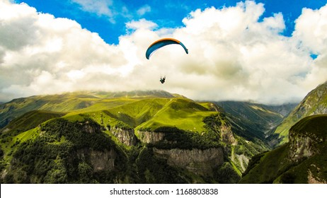 Paraglider silhouette flying over Caucasus mountains. Beauty world. Svanetia, Georgia, Europe.