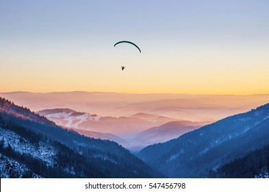 Paraglider silhouette flying over misty mountain valley in beautiful warm sunset colors - sport, active wallpapers full of freedom. Background with space for your montage