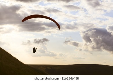A paraglider is silhouetted against the sky over Edale Valley in the Peak District, Derbyshire. The pilots gain lift from the strong updraft that occurs on windward hill slopes.