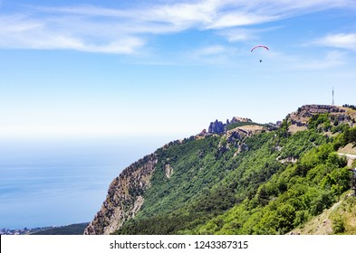 Paraglider soaring above the mountain top. Russia, Republic of Crimea. 06.13.2018. Paraglider flight over Ai-Petri mountain