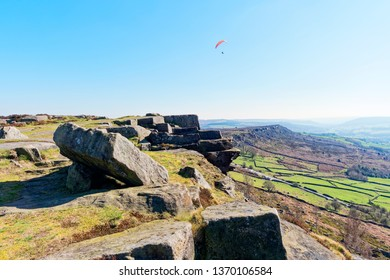 Paraglider soaring on Curbar Edge in the Derbyshire Peak District on a bright hazy spring day.