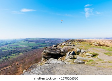 Paraglider soars over Curbar Edge, in the Derbyshire Peak District on a hazy spring day.