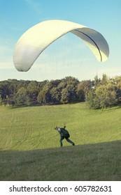 Paraglider is starting  his flight.