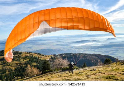 Paraglider is starting  to start his flight. Looking at beautiful valley below with clouds and mist.