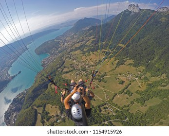Paraglider tandem flying over blue Lake