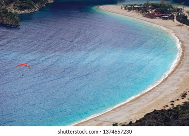 Paraglider tandem flying over the Oludeniz Beach and bay at idyllic atmosphere. Oludeniz, Fethiye, Turkey. Lycian way. Amazing Blue Lagoon detail. Summer and holiday concept.