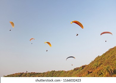 Paragliders against the blue sky. Bright paragliders fly in the sky. Extreme sport. Extreme. India, Goa.