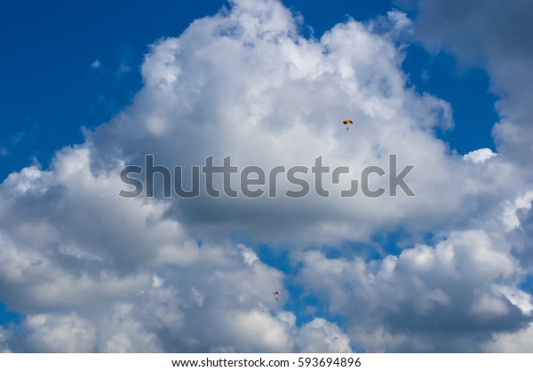 paragliders in flight in the sky with clouds