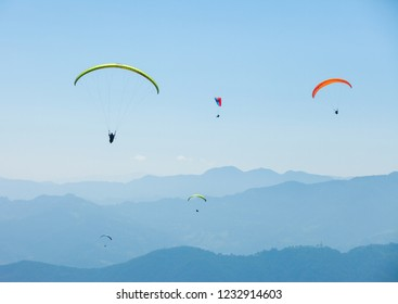 Paragliders float over the mountains near Pokhara, Nepal