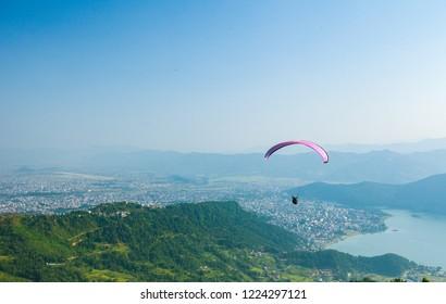 Paragliders float over Pokhara, Nepal's Fewa Lake and Lakeside tourist area