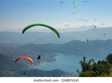 Paragliders float over Pokhara, Nepal's Fewa Lake and Lakeside tourist area
