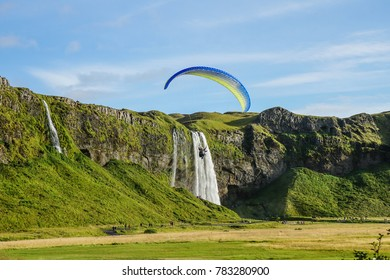 paragliders fly in the blue sky at Skógafoss Iceland with variation formation