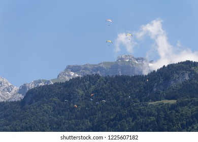 Paragliders flying above the forests and mountains of Col de la Forclaz above Lake Annecy France