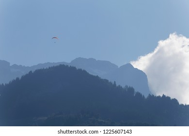 Paragliders flying in the early morning mists in amongst the mountains above Lake Annecy France