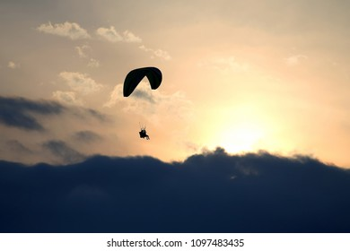 Paragliders flying on the wing against the sun in the clouds