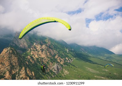 Paragliders are flying over mountains in cloudy summer day over the Chegem gorge, Caucasus
