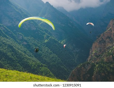 Paragliders are flying over mountains in summer day over the Chegem gorge, Caucasus